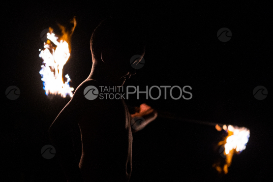 BORA BORA, PORTRAIT OF POLYNESIAN boy WITH FIRE TORCH AT NIGHT