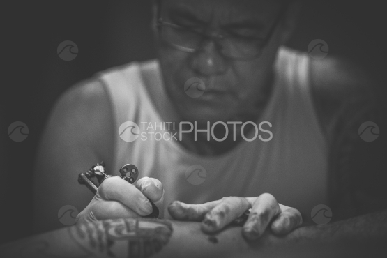 Bora Bora, tattoo artist working on arm of polynesian man