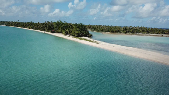 Aerial view by drone of the land of an atoll, 4K UHD