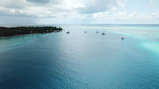 Aerial view by drone of atoll and sail boats anchored in the lagoon, 4K UHD