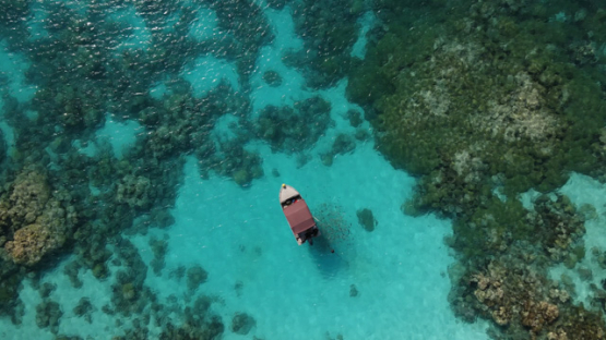 Rangiroa, aerial view of a small motor boat in the lagoon, 4K UHD