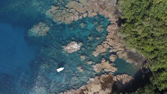 Tahiti, aerial view of Te Pari, boat near the reef, 4K UHD