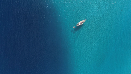 Moorea, aerial view of a sail boat anchored in the blue lagoon, 4K UHD
