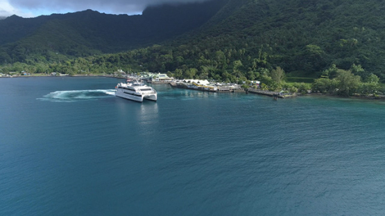 Moorea, aerial view of a ferry boat leaving the bay of Vaiare, 4K UHD