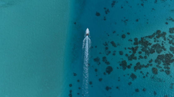 Tahaa, aerial view above a motor boat navigating in the lagoon, 4K UHD