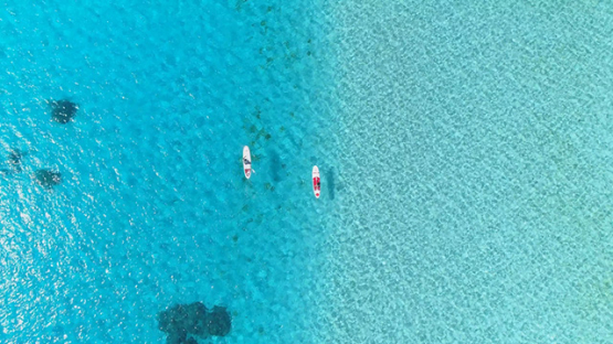 Bora Bora, aerial view above a couple of paddle boarders on the lagoon, 4K UHD