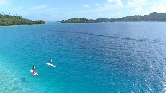 Bora Bora, aerial view of a couple of paddle boarders on the lagoon, 4K UHD