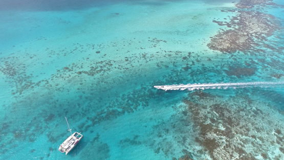 Bora Bora, aerial view of boat navigating in the lagoon, 4K UHD