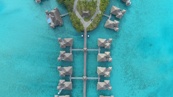 Bora Bora island, aerial view above a luxury overwater hotel in the lagoon, 4K UHD