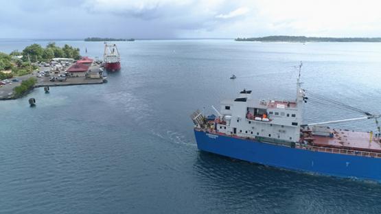 Bora Bora, aerial view of a cargo ship leaving Faanui dock, 4K UHD