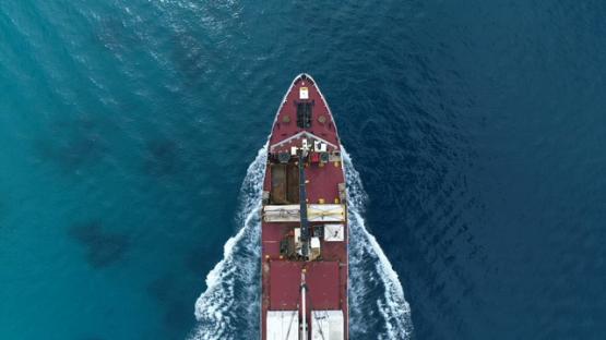 Bora Bora, aerial view above a cargo ship navigating in the lagoon, 4K UHD