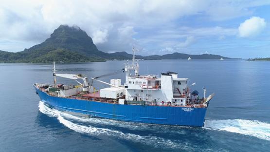 Bora Bora, aerial view of a cargo ship navigating in the lagoon, 4K UHD