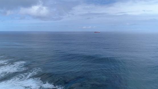 Bora Bora, aerial view of a cargo ship navigating in the ocean, 4K UHD