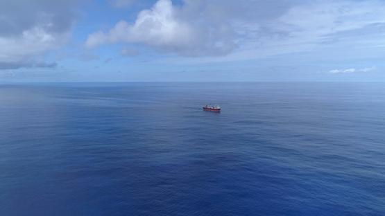 Bora Bora, aerial view of a cargo ship navigating on the ocean, 4K UHD
