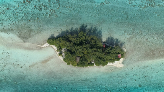Bora Bora, aerial view above a little islet surrounded by turquoise lagoon, 4K UHD