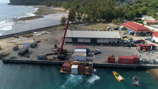 Rurutu, aerial view of a barge unloading container on the dock of the island, 4K UHD