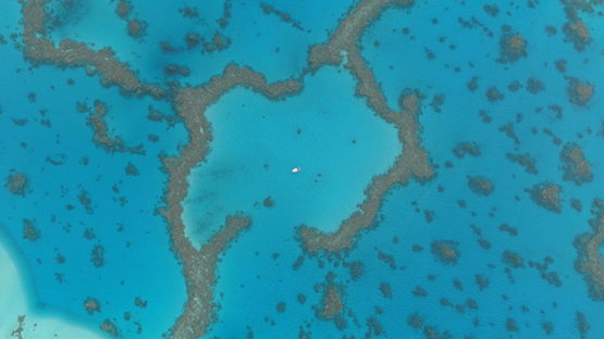 Tubuai, aerial view of a boat surrounded by the coral reef in the lagoon, 4K UHD