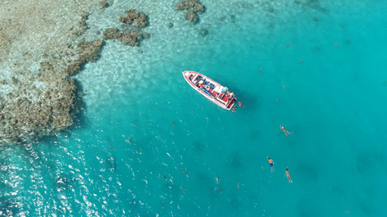 Rangiroa, aerial view above tourists swimming in the lagoon , 4K UHD