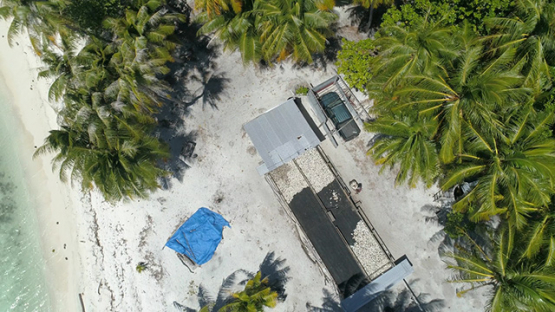 Rangiroa, aerial view of a man working on copra culture on an islet, 4K UHD
