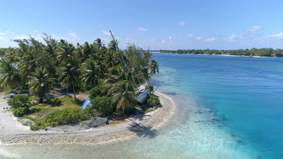 Rangiroa, aerial view of the pass Avatoru and beached sailboat, 4K UHD