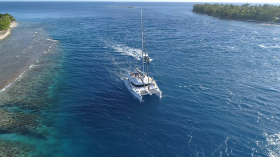 Rangiroa, aerial view of a catamaran navigating in the Tiputa pass, 4K UHD