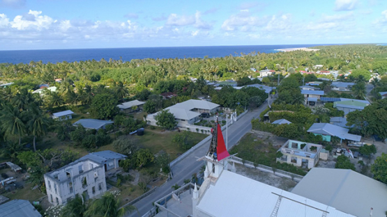 Rangiroa, aerial view of workers on the roof of the bell tower of the church of Tiputa, 4K UHD