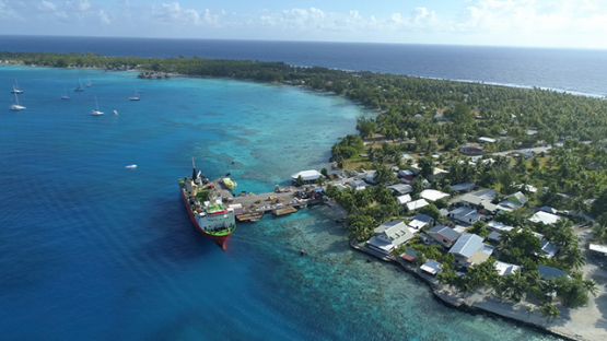 Rangiroa, aerial view of a cargo ship docking near Tiputa Pass, 4K UHD