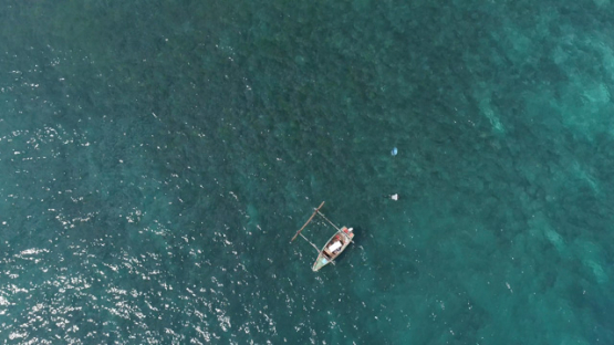Hiva Oa, aerial view above spearfisher and his outrigger in the bay near Puamau, 4K UHD