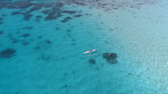 Bora Bora, aerial view of a polynesian rowing in an outrigger canoe in the lagoon, 4K UHD