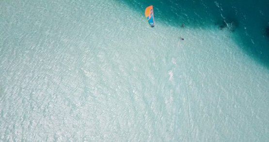 Tetiaroa 4k drone, aerial view of a kite surfer jumping over the blue gradient of the lagoon