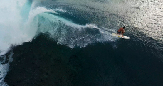 Tahiti 4K drone, aerial view following a surfer in Teahupoo wave