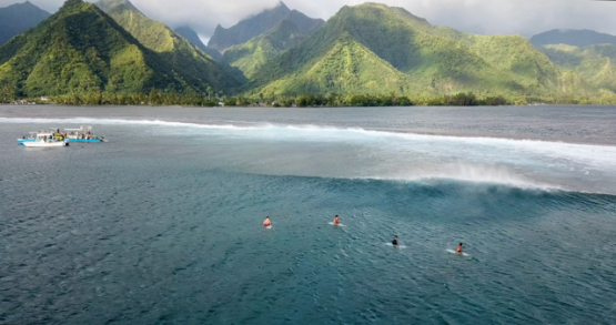 Tahiti 4K drone, aerial view of the back side of Teahupoo wave with surfers waiting in foreground