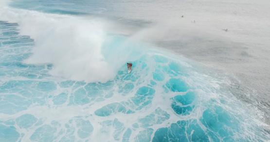 Tahiti 4k drone, aerial view of pro surfer in a Teahupoo barrel