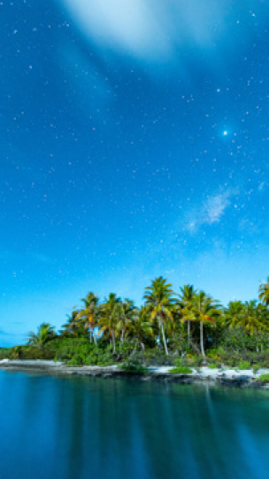Tikehau, vertical stary timelapse of a moonlight rise over a motu