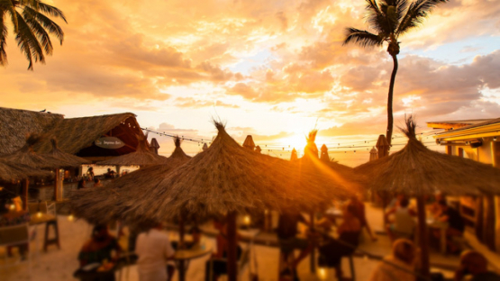Tahiti, timelapse of a crowdy bar terrace with a colored sunset  4K UHD
