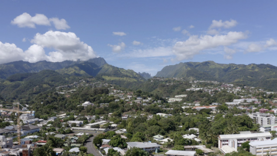 Aerial drone view of Tahiti, town of Arue and mountains in the background, 4K UHD